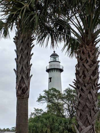 A lighthouse between two palm trees
